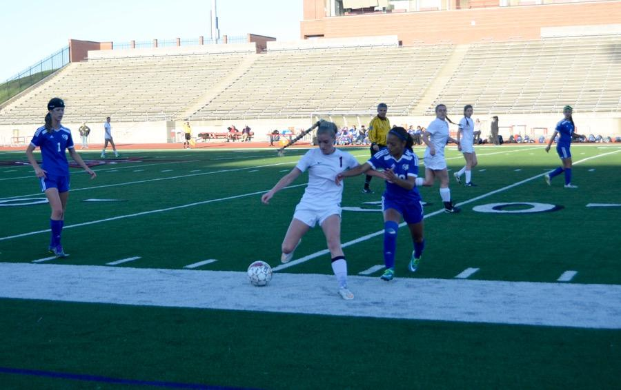 Coppell+High+School+senior+Shay+Johnson+fights+against+Duncanville+for+the+soccer+ball+on+March+24+at+Buddy+Echols+field.+Coppell+Cowgirls+defeated+Duncanville+1-0+in+the+first+round+of+playoffs.