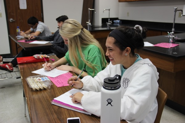 Coppell+High+School+sophomores+Angela+Varela+and+Avery+Zaves+take+notes+over+stoichiometry+%28the+relationship+between+different+quantities+of+substances+in+a+reaction%29+while+eating+cookies+on+Monday+in+teacher+Hanna+Glidewell%E2%80%99s+class.+Chemistry+classes+are+baking+cookies+to+help+aid+their+learning+in+stoichiometry+and+mole+conversions.+