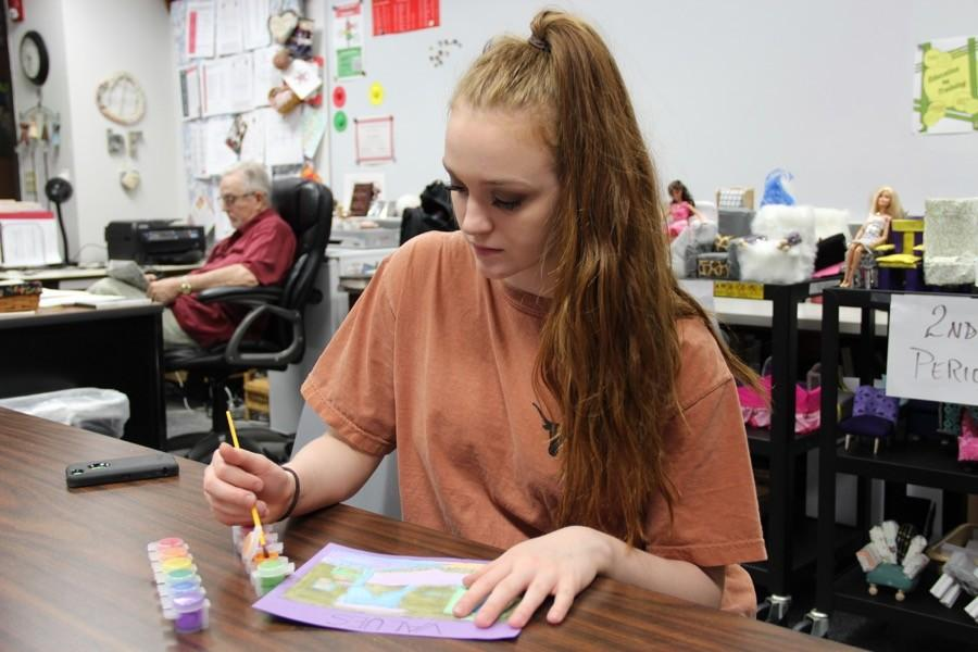 Coppell High School sophomore Sarah Wales paints different color schemes on a room in Beckey Richards's interior design class on March 9. Wales interns for a local interior designer in hopes of becoming one after she graduates college along with being a professional dancer.