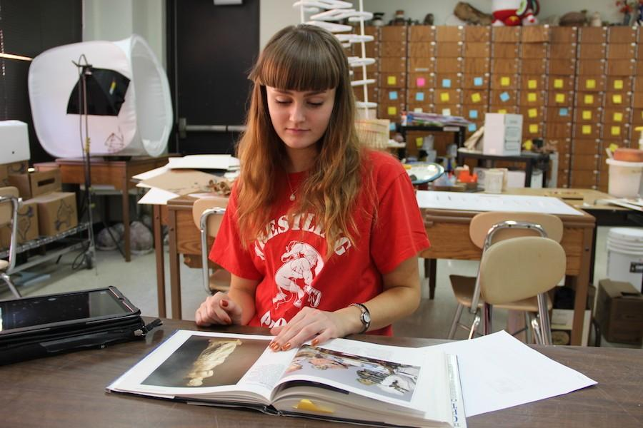 Coppell High School senior Taylor Stiff reads a book over 3D design sculptures in Tamera Westervelt's Sculpture/AP 3D Design class on Wednesday. Stift has been looking through different art books the past couple of days to get a new idea for her next project.