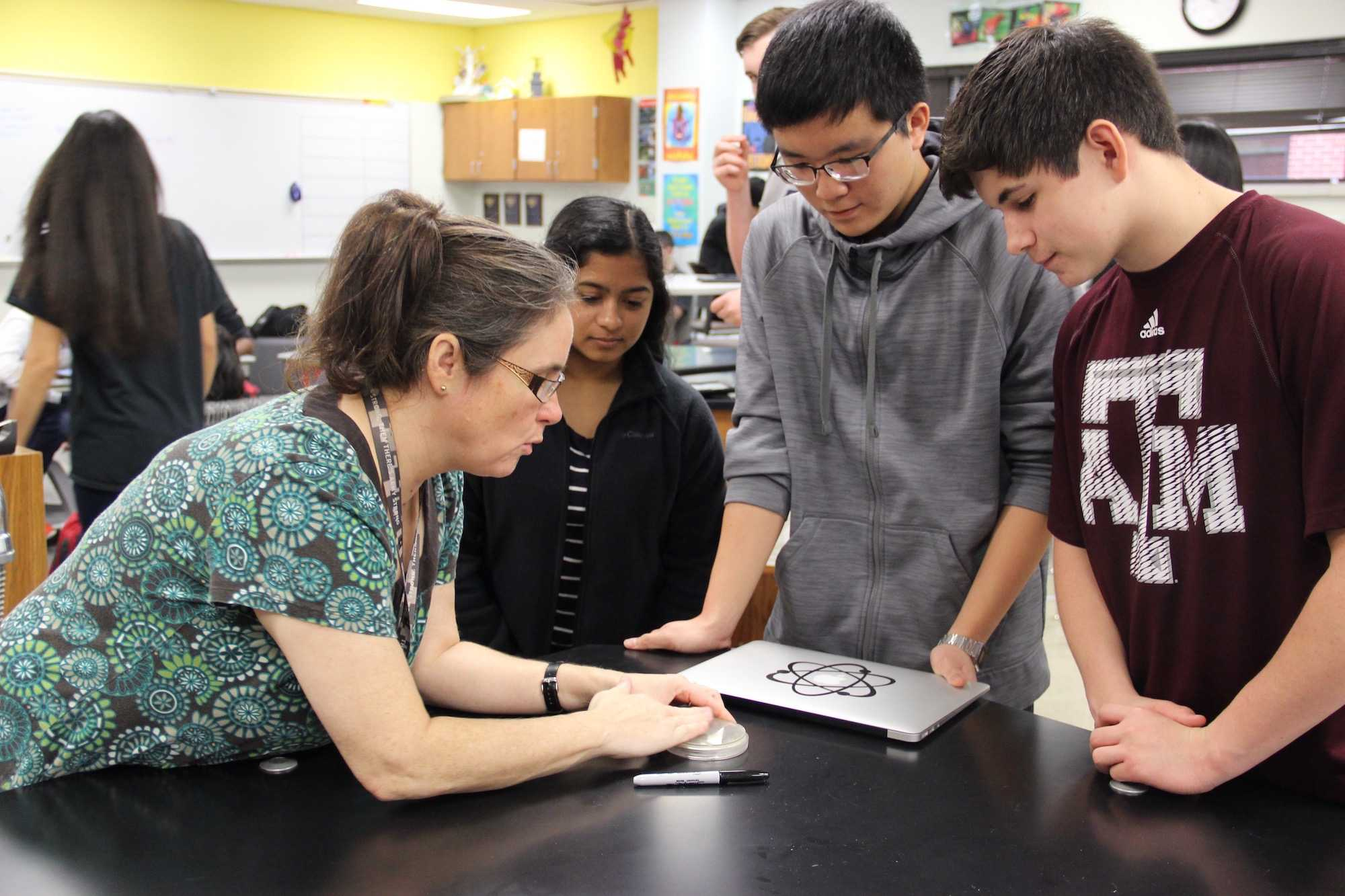 AP Environmental science teacher Cathy Douglas shows Holly Anderson's environmental science class how to correctly use petri dishes on Friday morning. Douglas was voted for the February 2016 Teacher of the Month.