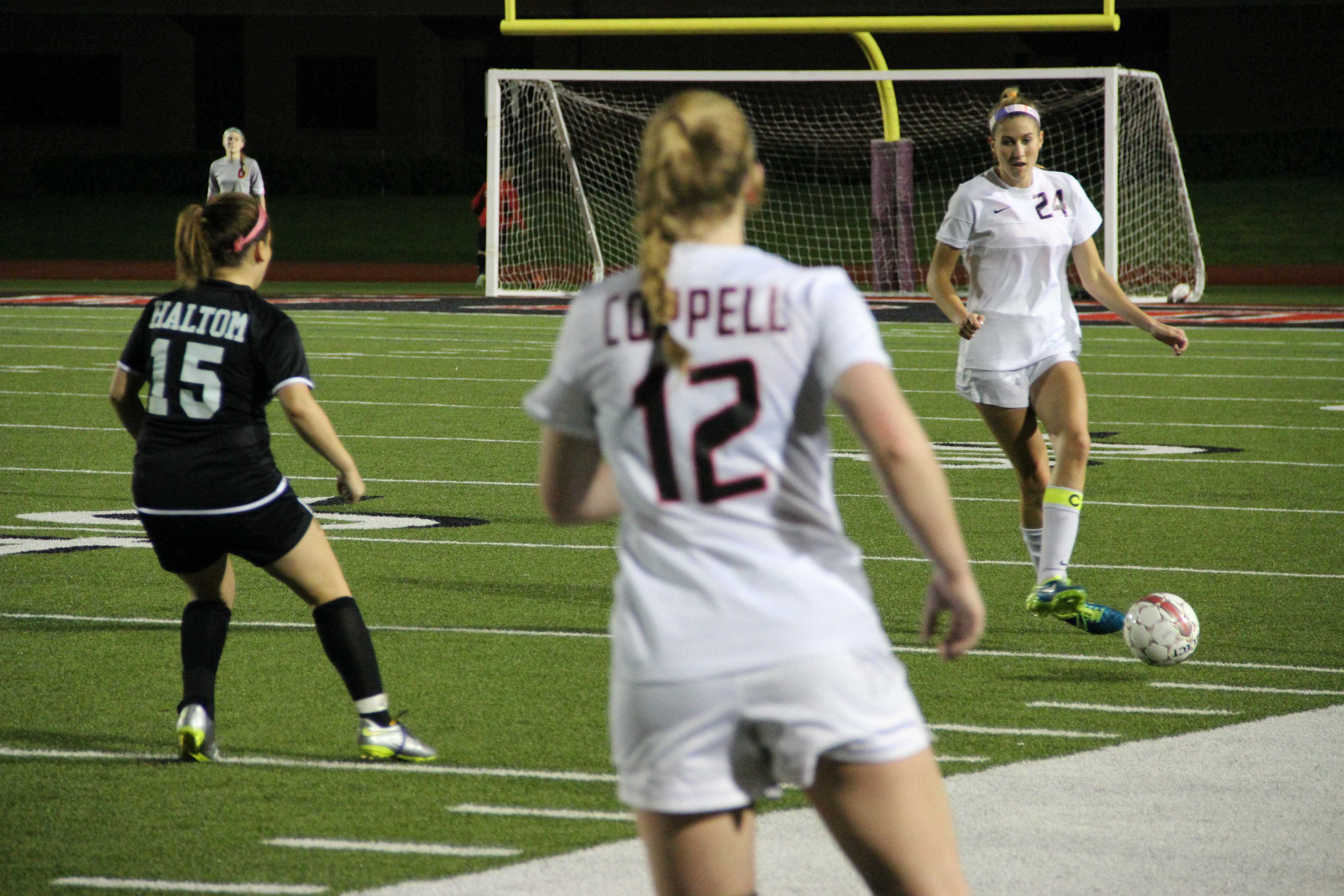 Coppell senior Emma Jett passes to senior Caitlyn Hiller during the first half of Friday's game against Haltom. Jett scored two goals as the Cowgirls cruised to  a 12-0 win. Photo by Ayoung Jo.