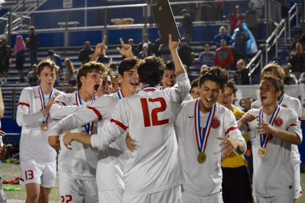 The Coppell Cowboys soccer teams celebrates senior Brandon Bohn's Most Valuable Player award on Saturday night at Birkelbach Field in Georgetown. The Cowboys defeated Lake Travis, 6-1, in the state championship match, ending their undefeated season with a record of 24-0-2.