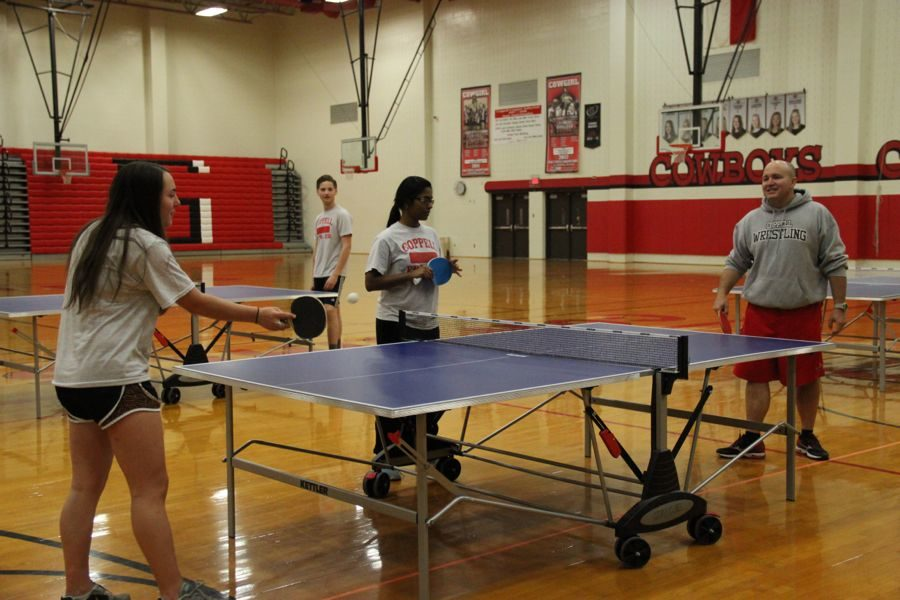 Coppell High School senior Kelly Risch competes against, table tennis teacher Chip Lowery on Monday. Lowery teaches the students all semester about different techniques and rules to strengthen their pingpong abilities.