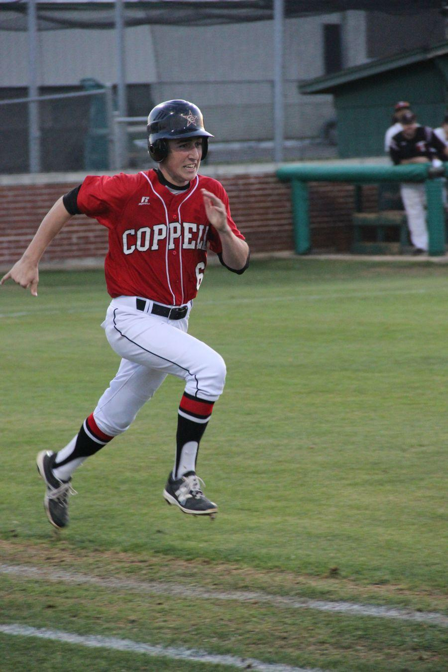 Coppell+High+School+junior+Nathan+Reedy+runs+to+first+base+during+the+baseball+game+on+Monday.+Cowboys+beat+the+Trojans+8-2+at+Trinity+High+School.+%0A
