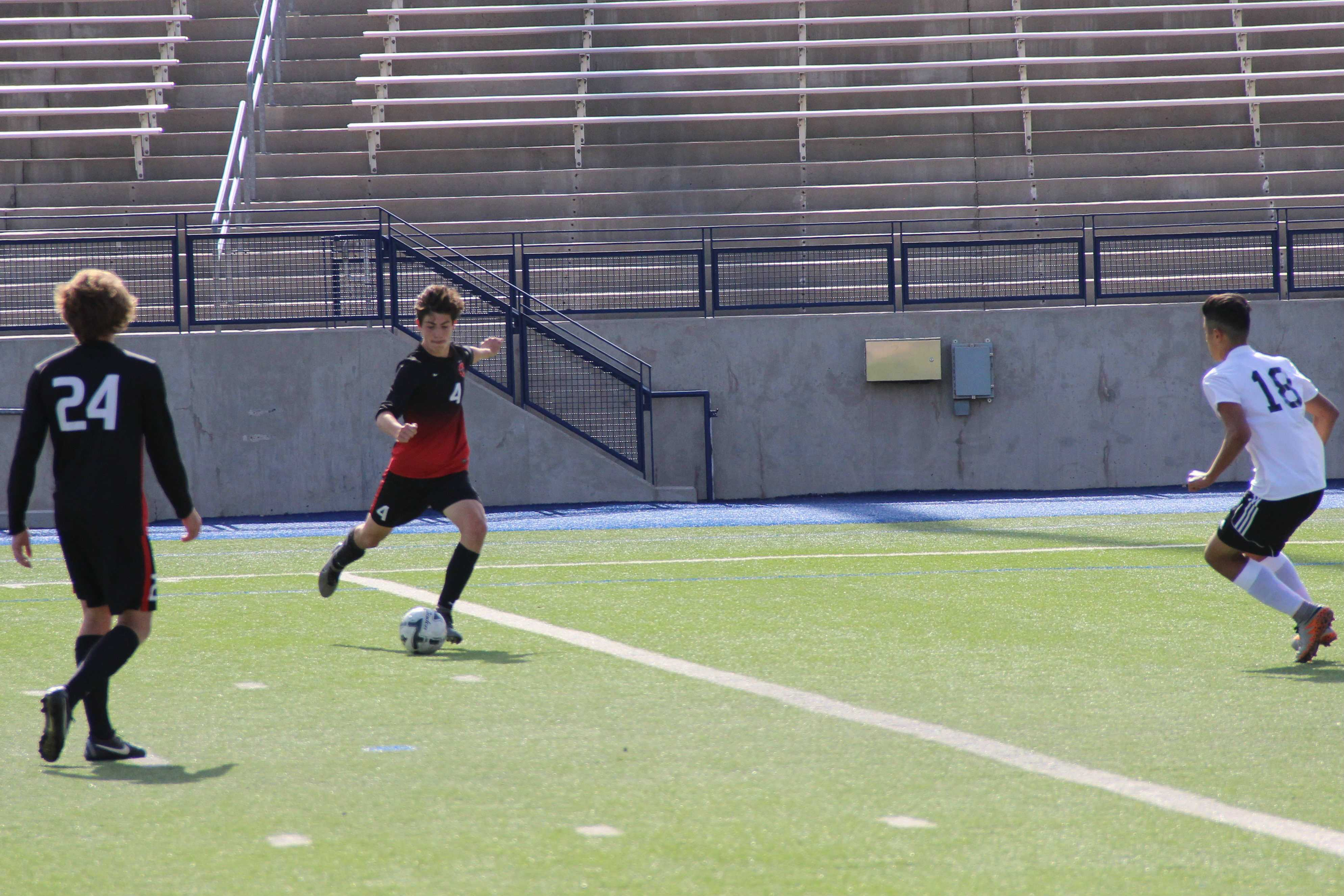 Sophomore forward Wyatt Priest strikes the ball in the second half of the Cowboys' 3-0 victory over El Paso Socorro on Friday, April 8. Priest scored his third and fourth goal of the playoffs to boost the Cowboys over the Bulldogs.