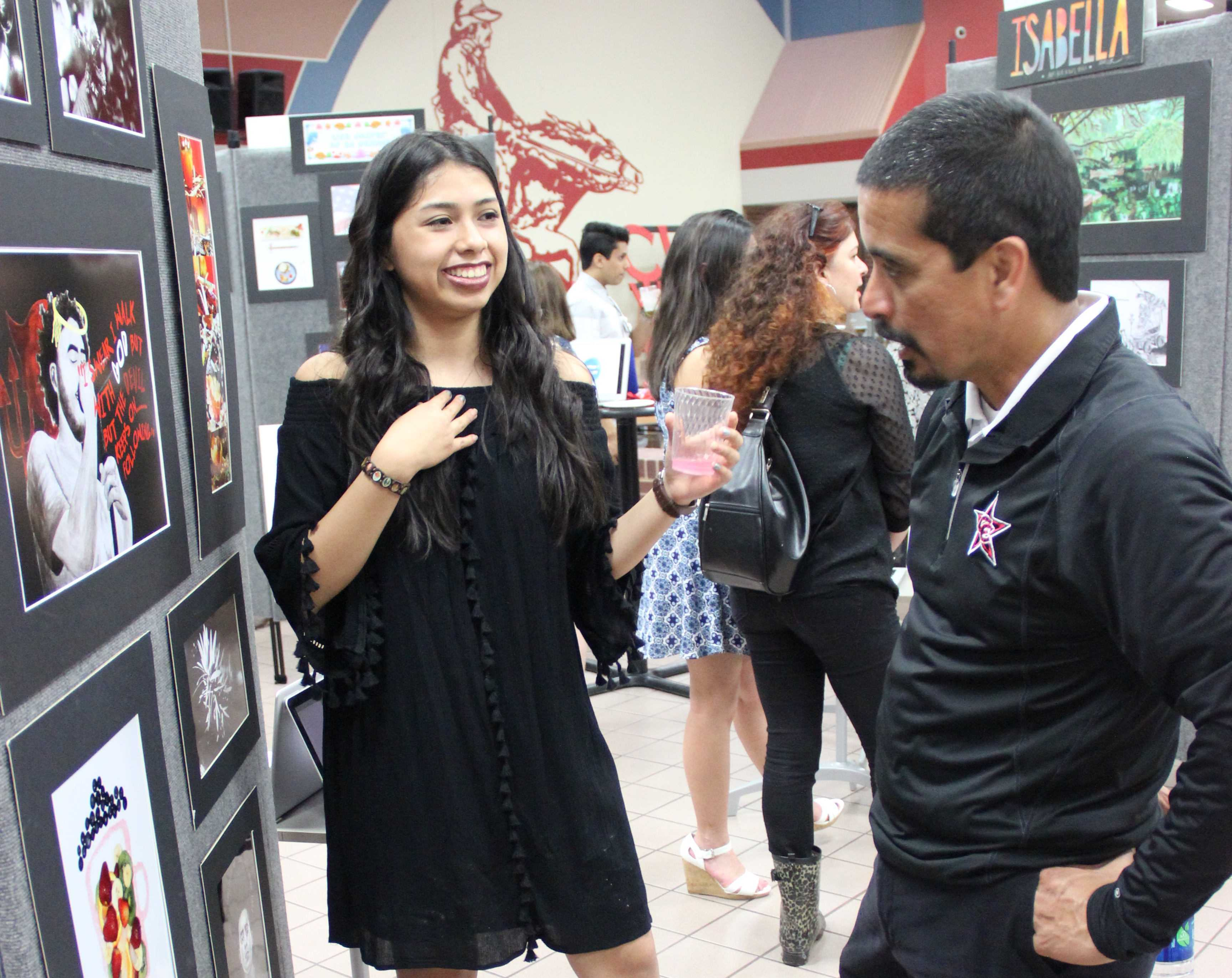 Coppell High School junior Giuliana Vargas presents her artworks to principal Mike Jasso during the AP/IB art showcase on Thursday. Vargas's chosen concentration was two-dimensional art.