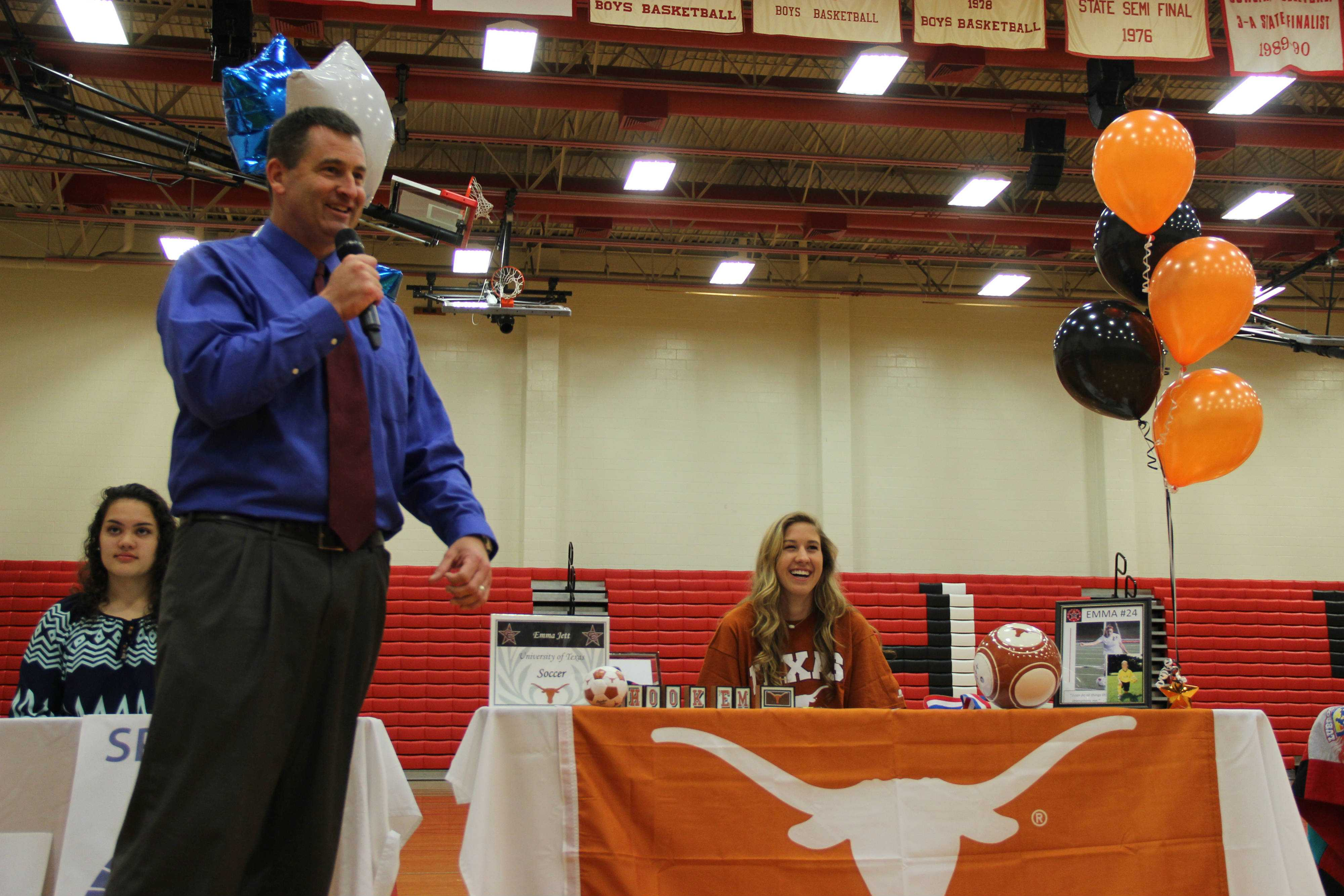 Senior girls soccer player Emma Jett laughs as former coach Chris Stricker tells a story to the crowd about Jett. Jett signed to play soccer at the University of Texas. Photo by Ale Ceniceros.