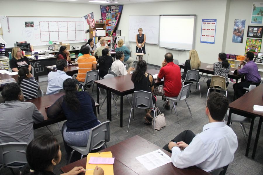 Coppell High School math teacher Ginger Smith discusses the upcoming school year with parents at Curriculum Night on Monday. Parents were able to walk their child's schedule and observe their classwork and teachers during the first week of school.