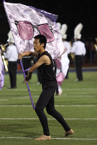 New Tech High @ Coppell senior and color guard member Dennis Shen performs in the halftime show during Friday night's football game against McKinney Boyd at Ron Poe Stadium. Shen was involved in bans for 6 years before joining color guard for the 2016-2017 school year. Photo by Amanda Hair.
