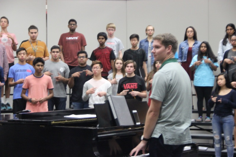 Coppell High School choir associate director Adam Gilliland warms up with the A Capella choir during Josh's Brown fifth period class. A big competition (Texas Music Educators Association) takes place this February, Gilliland helps Brown and the choir to be successful. Photo by Ale Ceniceros