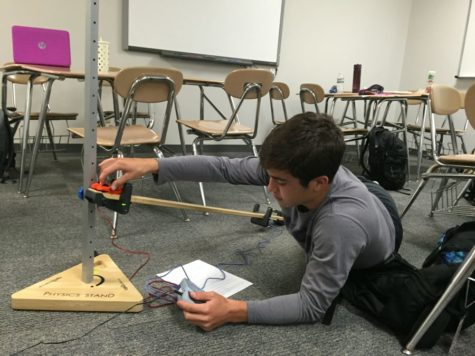 Coppell High School junior Marshall Board releases a toy car to measure its acceleration for a lab during Wes Cowling's second period physics class on Tuesday. Classes are learning the basic terms on motion leading to velocity and acceleration formula's.