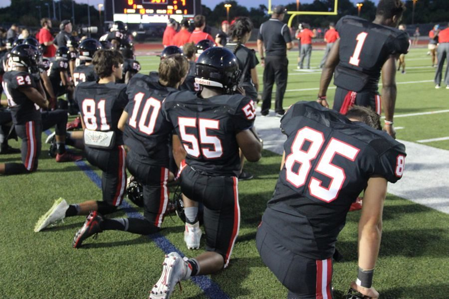 Coppell+High+School+varsity+football+players+kneel+while+Coppell+player+Skyler+Siedman+is+injured+on+the+field+during+Friday+night%E2%80%99s+game.+Allen+claimed+a+victory+over+Coppell+with+a+final+score+of+42-20+at+Buddy+Echols+Field.