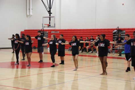 Coppell High School junior Kryslyn and other students listen to Hayley Mitchell as she shows the Dance I class how to perform certain moves, last Wednesday. The dance students are required to prepare for their dance on Friday.