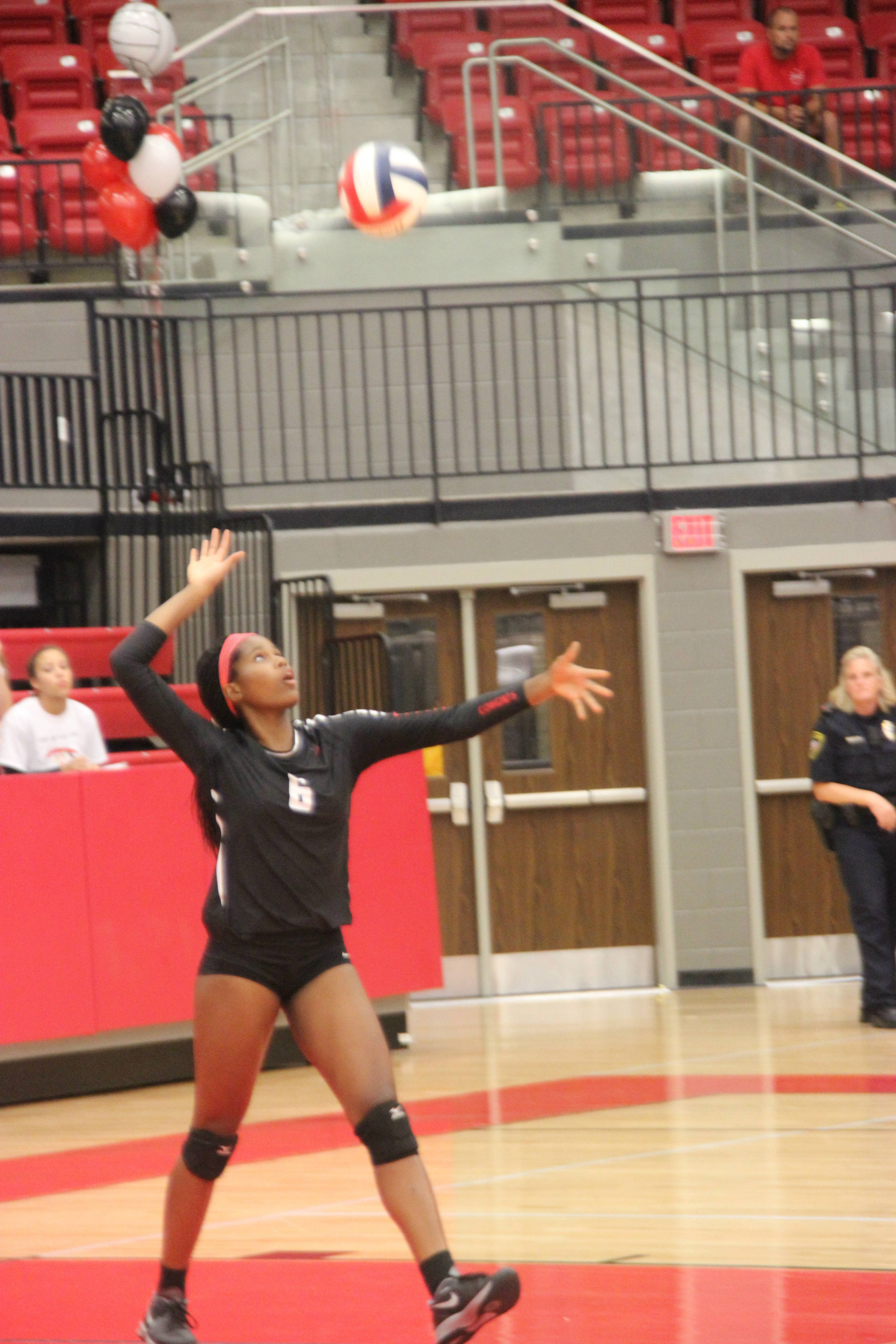 Coppell High School sophomore Amanda Osuji serves the ball during the third set on Tuesday night against Lake Highland. The Coppell Cowgirls defeated Lake Highland, winning three out of the five sets played in the Coppell High School arena. Photo by Katie Wiener.