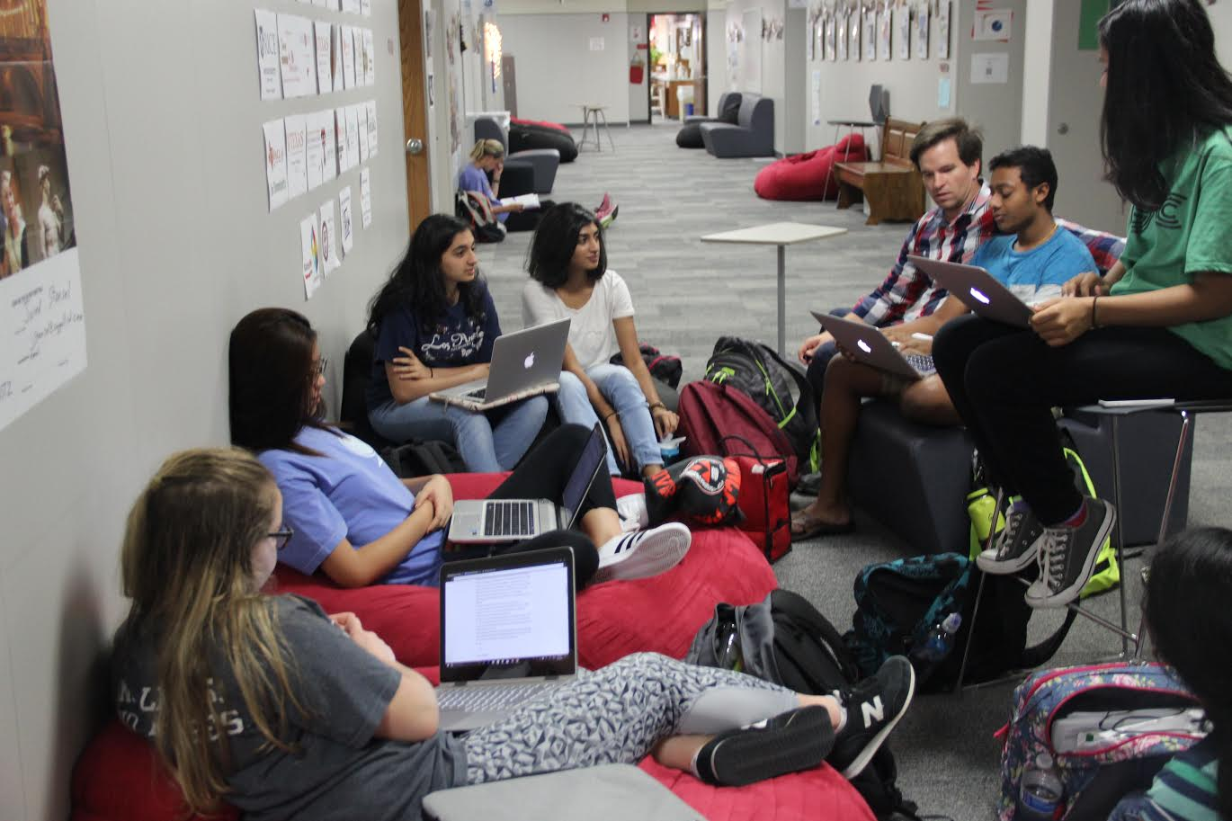 The Coppell High School KIVA club members gather in D hall with their sponsor, IB Economics teacher Jared Stansel, for their weekly meeting. The group discussed club elections and how they would choose what small businesses to fund.