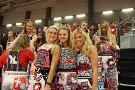 Coppell High School seniors (left to right) Maddie Webber, Jessica James and Nicolette Boaz show off their Coppell-colored senior overalls in the senior section at the pep rally against Allen High School last Friday in the new arena. The senior overalls, a tradition of Coppell, is a pair of overalls each senior, typically found more on females, makes that shows off their interests, school activities, mementos, and colleges that is worn on Fridays with home football games to show their school spirit. Photo by Hannah Tucker.