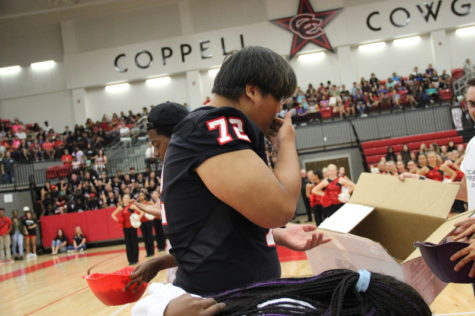 Coppell High School senior Ji Won Seo wipes off his face after representing the senior class and digging items out of a jelly as one of the games played at the pep rally against Allen High School last Friday in the arena. Each pep rally, the cheerleaders set up small games to hype up the crowd and allow friendly competition between each grade level. Photo by Hannah Tucker.