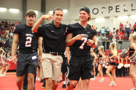 Coppell High School junior Cole Bryant walks with his teammate, senior football captain Joe Fex and senior quarterback Brady McBride through the line of cheerleaders and into the pep rally against the Allen Eagles last Friday in the new arena. Cole Bryant has the position of assistant football coach and travels everywhere with the team, cheering and encouraging them on. Photo by Hannah Tucker.