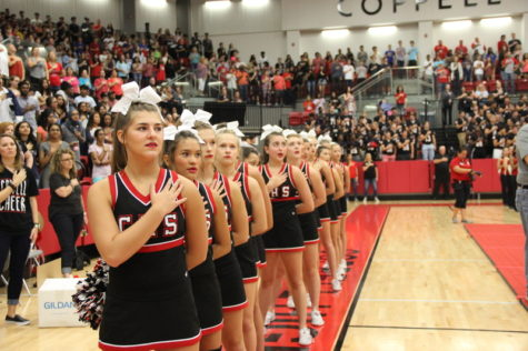 Coppell High School sophomore Gracie Flynn stands in front of the line with her hand over her heart and pompoms behind her back to show respect while the acapella team recites the National Anthem at the pep rally against Allen High School last Friday in the arena. Flynn is one of the sophomore cheerleaders that has made it onto the varsity squad this 2016-2017 year. Photo by Hannah Tucker.