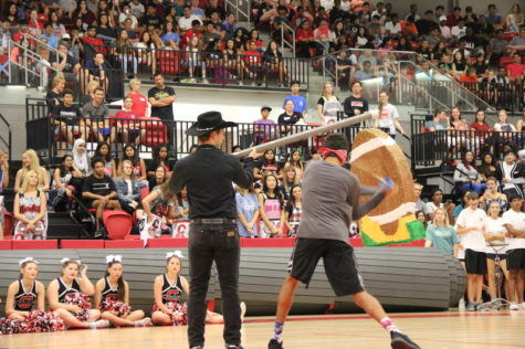 Coppell High School sophomore Noah Snelson swinging to hit the pinata brought by the Silver Spurs as an activity at the pep rally against the Allen Eagles last Friday in the arena. Blindfolded, Snelson took a swing and instead of hitting the pinata, hit the Silver Spur holding the pinata square in the stomach and groin area. Photo by Hannah Tucker.