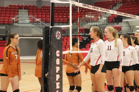 """Coppell High School senior outside and right hitter Grace Heaton and senior outside hitter Katie Herklotz high five the opposing team to shop good sportsmanship at the end of the game against W.T. White Tuesday night in the CHS arena. """"Every game counts the same. I think there's a mindset that if it's not a top 10 team that they don't prepare or don't stay focused enough and we really wanted our girls to keep that focus and take care of our side of the net,"""" Coppell Coach Julie Green explains. Photo by Hannah Tucker."""