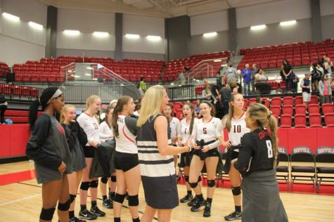 Coppell High School volleyball coach Julie Green greets her team after the victory and jokes around with them after one of the girls starts crying from laughter after the game against W.T. White Tuesday night in the arena. It was a very laid back game and atmosphere, seeing as W.T. White isn't one of Coppell's major rivals. The Cowgirls won each set 5-3, 24-5, and 25-7. Photo by Hannah Tucker.