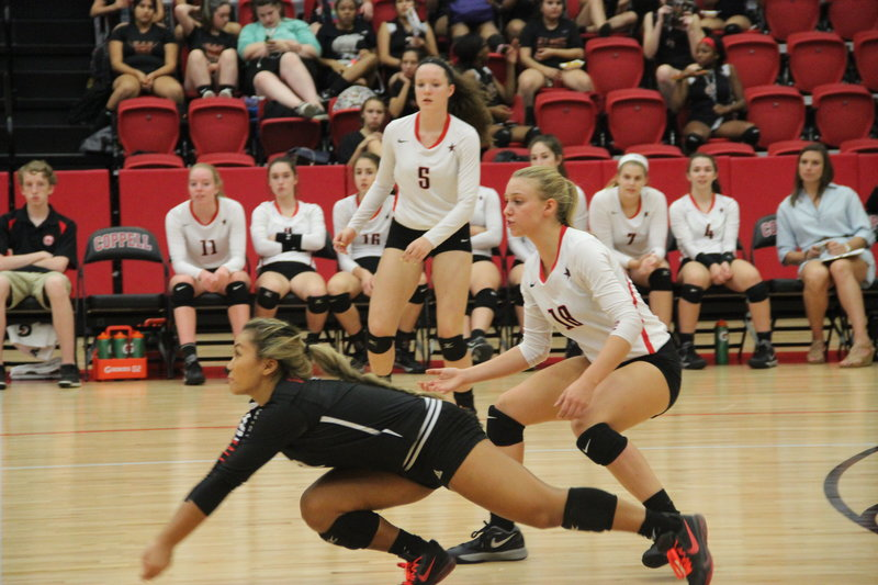 Coppell+High+School+senior+libero+Lauren+Lee+dives+to+save+the+ball+from+hitting+the+ground+while+junior+defensive+specialist+Izzy+Hall+and+junior+outside+and+rightside+hitter+Amanda+Colon+try+to+rush+to+her+aid+at+the+varsity+game+against+W.T.+White+Tuesday+night+in+the+arena.+The+Cowgirls+won+each+set+25-3%2C+24-5%2C+and+25-7.