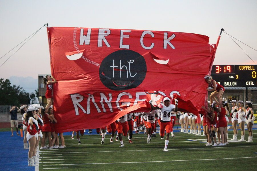 The+Coppell+Cowboys+run+through+the+%E2%80%9CWreck+the+Rangers%E2%80%9D+sign+made+by+the+CHS+cheerleaders+before+Friday+night%E2%80%99s+away+game+at+Postell+Stadium+against+the+Jesuit+Dallas+Rangers.+The+Cowboys+lost+41-10+their+first+district+game.