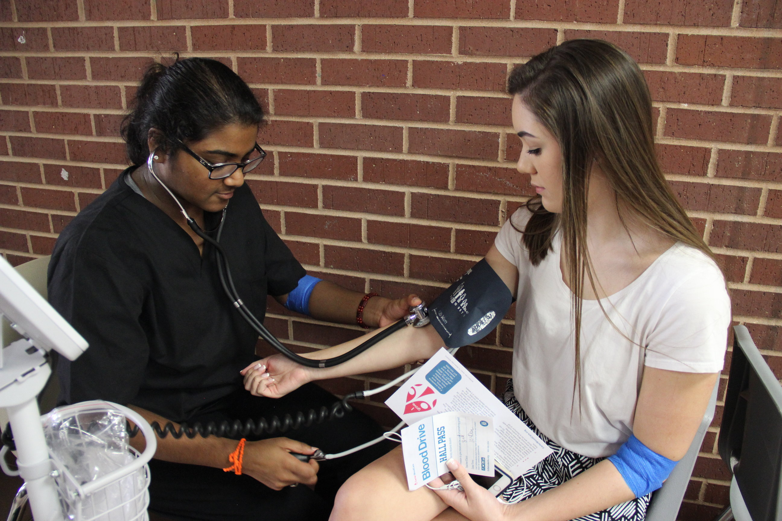 Coppell High School junior Navya Peddireddy checks senior Morgan Bryan's pulse after Bryan gave blood in the Coppell High School small gym on Tuesday. Students in the medical endorsement and Red Jackets helped out at the blood drive. Photo by Wren Lee