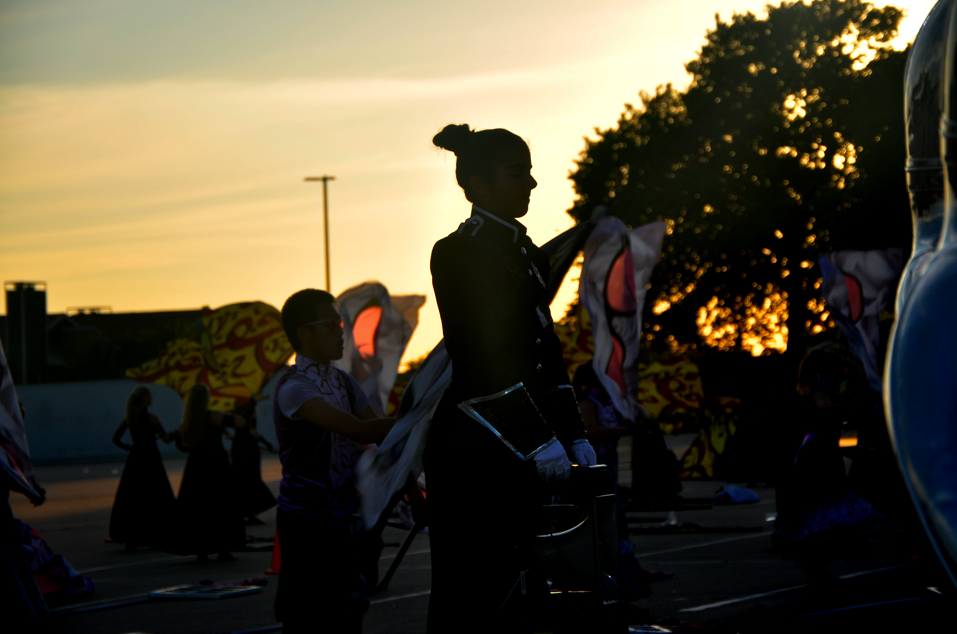 """Coppell High School junior Ashna Pathan looks on as Coppell Marching Band warms up for its UIL Region 31 Marching Band Contest at Pennington Field in Bedford on Tuesday. The band took home sweepstakes for its competition show """"Now I See."""" Photo by Amelia Vanyo"""