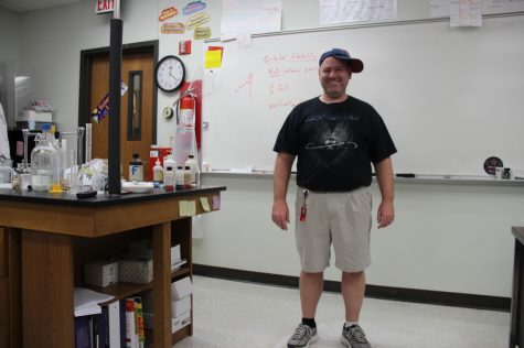 "Coppell High School chemistry teacher Kevin Brimage wears his mixed and uncoordinated articles of clothing for Red Ribbon theme week last Monday in class. ""It's my gangster, golfer, and rocker look,"" Brimage explains, pointing to his rock band T-shirt, golfer shorts and sideways ball cap. Photo by Hannah Tucker."