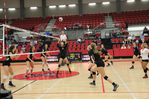 Coppell High School sophomore Stella Yan sets the ball as teammates run to spike it over the net during the homecoming game Friday night in the CHS arena. The Cowgirls won 3-0 against the J.J. Pearce Mustangs, remaining undefeated in the district with a  6-0 district record.