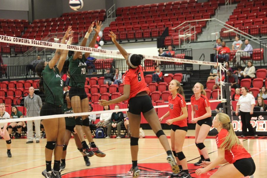 Coppell High School sophomore Amarachi Osuji tips the ball during the second set of the game Friday in the CHS arena. After three sets of playing Friday night the Cowgirls took the victory and won all three sets.