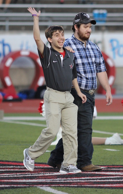 Coppell+High+School+senior+Marcus+Garza+%28left%29+and+his+brother+%28right%29+walk+down+Buddy+Echols+Field+at+Coppell+High+School+as+the+homecoming+court+is+announced+on+Sept.+30.+Both+homecoming+king+and+queen+were+announced+during+halftime+of+the+football+game+against+J.J.+Pearce.+Photo+by+Amanda+Hair.+