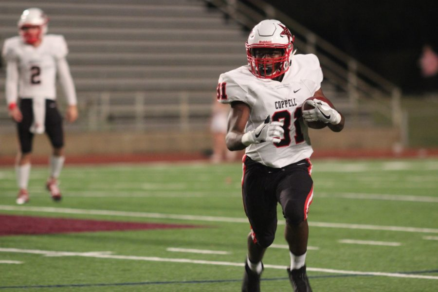 Coppell senior running back Chuk Esedebe sprints to the outside on a run in the fourth quarter. Esedebe had a six yard touchdown run in Coppell's 40-14 win over W.T. White at Loos Stadium. Photo by Amanda Hair.