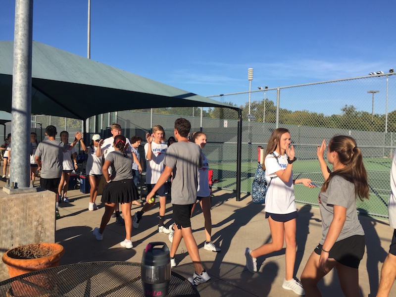 Coppell+High+School+varsity+tennis+players+exchange+high-fives+with+Pierce+High+School+players+after+winning+10-0+on+Oct.+21.+The+Cowboys+will+advance+to+regionals%2C+hoping+to+continue+their+winning+streak