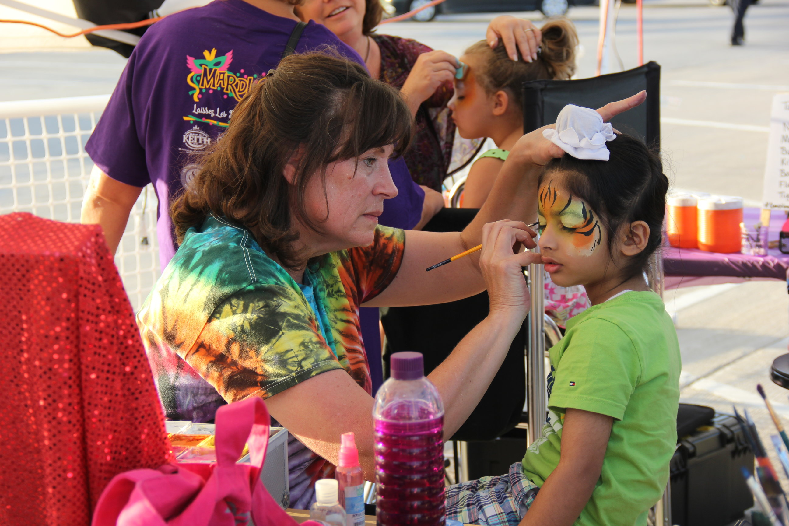 Young children's faces are painted to resemble colorful animals near the arts and crafts stations. This Saturday, Coppell partnered with Dodie's to hold its first annual Mardi Gras in the Fall event at the Square in Old Town Coppell.