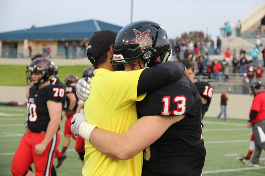 Coppell High School senior Ryan Jones shares a hug with assistant football coach Eric De Los Santos after the end of today's game at WISD Stadium. The Coppell Cowboys fell to the Round Rock Dragons with a final score of 49-45 in the regional semifinals.
