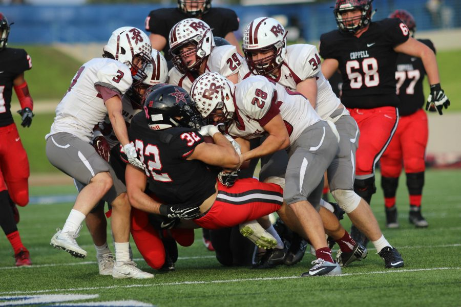 Coppell High School senior Bernardo Rodriguez gets tackled by multiple Round Rock players at the third quarter comes to a close at WISD Stadium. Round Rock ended the night with a 49-45 victory over Coppell, ending the Coppell Cowboys' season.
