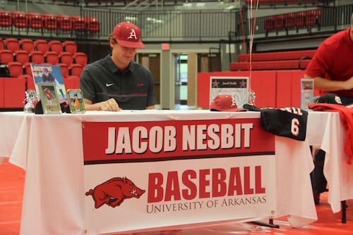 Senior Jacob Nesbit signs to Arkansas for baseball on Nov. 9, National Signing Day, in the Coppell High School arena. Five CHS students signed their letters of intent to play baseball in college, nine students signing in total.
