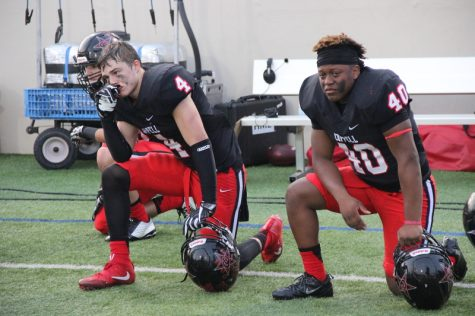 As the final quarter of Saturday's game comes to a close, Coppell High School sophomore TJ McDaniel (left) and senior Christian Green (right) watch the end of the game while kneeling on the sidelines. The Round Rock Dragons defeated the Coppell Cowboys with a final score of 49-45 at WISD Stadium, ending the Cowboys' season.