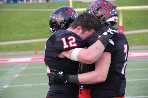 Coppell High School seniors Ryan Finglass (left) and Joe Fex (right) share a hug after the end of today's game at WISD Stadium. The Coppell Cowboys fell to the Round Rock Dragons with a final score of 49-45 in the regional semifinals.