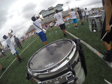 "The Coppell Band practices before the UIL State competition at  Heroes Stadium in San Antonio on Nov. 8. Rehearsing the first movement of the show, ""Rose Colored Glasses,"" senior snare drummer Eliana Yamouni attaches a GoPro to her drum harness to get an on-field level view. Photo by Hannah Tucker."
