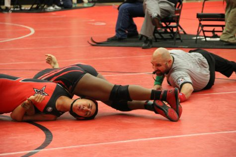 Coppell High School senior Alianna Laione gets pinned down by opponent from Liberty High School last Friday in the Coppell Arena. With a solid performance, the Coppell Cowboys girl's wrestling team places top three in multiple weight categories.