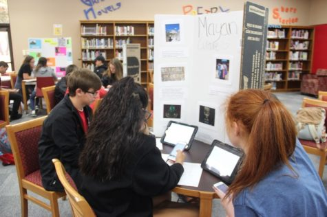 During third period on Tuesday, Coppell High School freshman Riley Orhearn and her group listen to music from the Mayan culture and observe the rest of the project in the CHS library. Students wrote down their personal feedback on each presentation for their World Geography class.