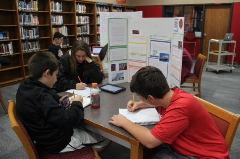During third period on Tuesday, Coppell High School freshman Michael Hudson observes a poster regarding the Mayan culture and writes down feedback for his group. Students were allowed to move around the library to observe the other students' presentations.