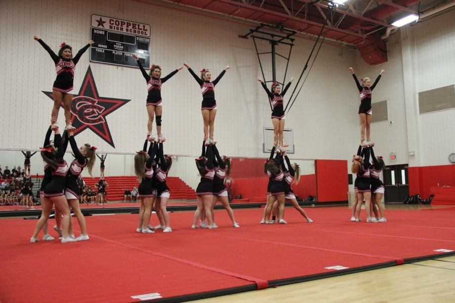 The Coppell High School varsity cheer team hits their stunt during the routine prepared for nationals. Varisty and the youth cheer teams performed for parents and friends on Wednesday in the CHS small gym.