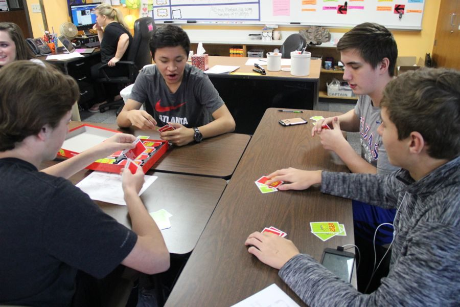 Coppell High School juniors Connor Martin, Ryan Lombardo, Josh Muñoz, Kyle Bennett (left to right) play Apples to Apples to engage in team building during Courtney Orloff's third period class on Tuesday. At the end of every six weeks, Orloff's classes take a day to get to know each other better and enjoy a laid back day.