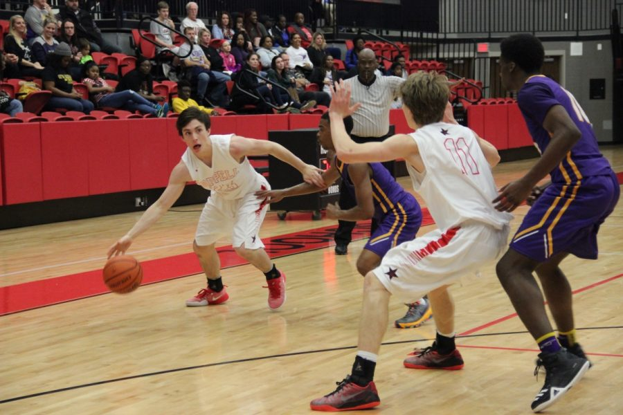 Coppell junior guard Alec Brinneman looks to pass to junior forward Kevin Galvin in the second quarter of the Cowboys game at the CHS arena on Friday night. The Cowboys defeated Richardson, 58-47 for their third district win of the season.